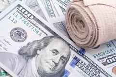 Billetes de banco colocados vendaje médico del dólar de EE. UU. Foto de archivo libre de regalías