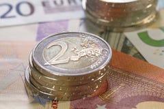 Billetes de banco con 2 pilas de 2 monedas euro Imagenes de archivo