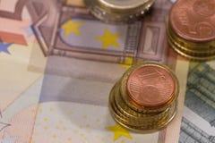 Billetes de banco con tres pilas de monedas Imagen de archivo libre de regalías