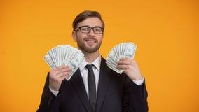 Billetes de banco confiados del dólar de la demostración del hombre de negocios y guiño, trabajo bien pagado, efectivo almacen de metraje de vídeo
