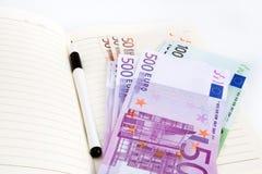 Billetes de banco, cuaderno y pluma euro Imágenes de archivo libres de regalías