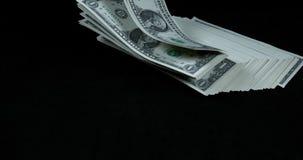 Billetes de banco de 1 dólar de EE. UU. que caen contra fondo negro, almacen de metraje de vídeo