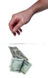 Billetes de banco de la mano y del dólar en agua Foto de archivo
