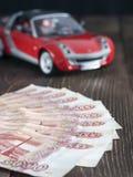 Billetes de banco de la rublo rusa en un fondo con el coche del juguete Foto de archivo