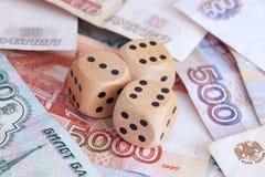 Billetes de banco de la rublo y dados de madera en ellos Fotos de archivo libres de regalías