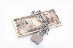 Billetes de banco de los yenes con una cerradura y una cadena Foto de archivo