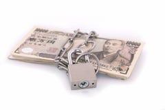 Billetes de banco de los yenes con una cerradura y una cadena Imagen de archivo