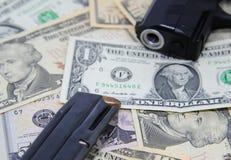 Billetes de banco del dólar con el arma y la revista Imagen de archivo