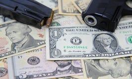 Billetes de banco del dólar con el arma y la revista Foto de archivo