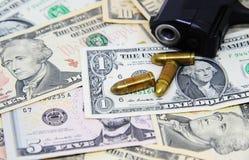 Billetes de banco del dólar con las pistolas y el arma Foto de archivo libre de regalías