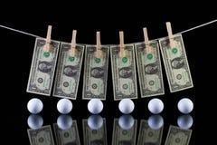Billetes de banco del dólar de EE. UU. y pelotas de golf sucios Imagenes de archivo