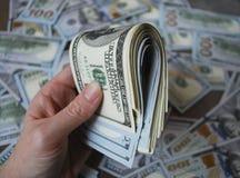 Billetes de banco del dólar del efectivo del control de la mano de la mujer Fotografía de archivo