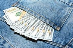 Billetes de banco del dólar en bolsillo de la parte posterior de los vaqueros Fotos de archivo