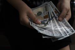 100 billetes de banco del dólar en manos del ` s de los niños Fotografía de archivo