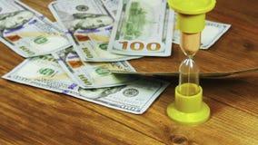 Billetes de banco del dólar que caen en una tabla y un reloj de arena de madera metrajes
