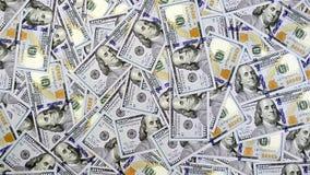 Billetes de banco del dólar que caen uno por uno en la superficie de la tabla cubierta con el dinero metrajes