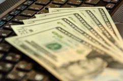 Billetes de banco del efectivo del dinero en el teclado del ordenador port?til D?lares americanos imagen de archivo