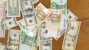 Billetes de banco del euro y del dólar que caen abajo a la tabla de madera almacen de video