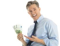 Billetes de banco emocionados del euro de Showing One Hundred del hombre de negocios Fotografía de archivo