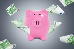 Billetes de banco euro alrededor de la hucha Imágenes de archivo libres de regalías