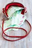 100 billetes de banco euro caen hacia fuera del bolso rojo Fotografía de archivo libre de regalías