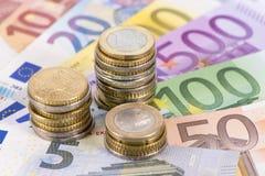 Billetes de banco euro con las monedas apiladas Fotos de archivo