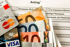 Billetes de banco euro con Mastercard y la tarjeta Visa en un formulario de inscripción alemán de pasaporte Imágenes de archivo libres de regalías