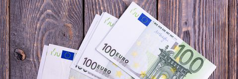 Billetes de banco euro del efectivo en un fondo de madera oscuro fotos de archivo
