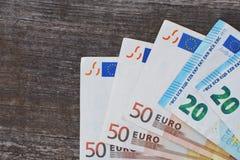 Billetes de banco euro en fondo de madera gris oscuro imagenes de archivo