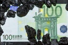 Billetes de banco euro en las pepitas crudas del carbón, cuentas en el carbón, poder del mone Imagenes de archivo