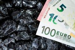 Billetes de banco euro en las pepitas crudas del carbón, cuentas en el carbón, poder del mone Foto de archivo