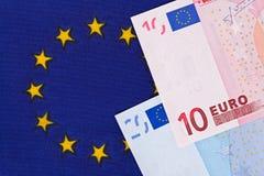 Billetes de banco euro en una bandera de unión europea Fotos de archivo