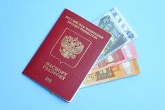 Billetes de banco euro invertidos en un pasaporte ruso extranjero en un fondo azul Viaje a Europa imagen de archivo