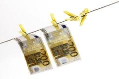 200 billetes de banco euro que cuelgan en cuerda para tender la ropa Fotos de archivo libres de regalías