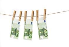 100 billetes de banco euro que cuelgan en cuerda para tender la ropa en el fondo blanco Fotografía de archivo