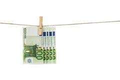 100 billetes de banco euro que cuelgan en cuerda para tender la ropa en el fondo blanco Fotografía de archivo libre de regalías