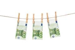 100 billetes de banco euro que cuelgan en cuerda para tender la ropa en el fondo blanco Foto de archivo libre de regalías