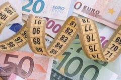 Billetes de banco euro y cinta métrica amarilla Imagenes de archivo