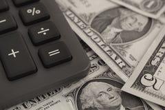 Billetes de banco de la calculadora y del dólar foto de archivo