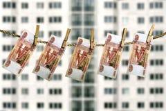 Billetes de banco de la rublo rusa que cuelgan en una cuerda para tender la ropa en la fachada borrosa de un fondo de la casa de  Fotografía de archivo