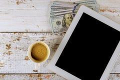 Billetes de banco de los dólares americanos de la tableta del negocio y taza de café en la tabla de madera imagenes de archivo