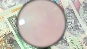 Billetes de banco polacos del zloty con la lupa Imagen de archivo libre de regalías