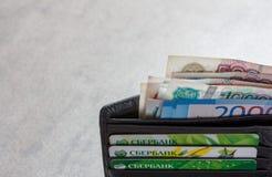 Billetes de banco rusos en denominaciones de 1000, 2000 y 5000 rublos y tarjetas de crédito Sberbank en un primer de cuero negro  Fotografía de archivo libre de regalías