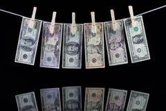 Billetes de banco sucios del dólar de EE. UU. que cuelgan de una cuerda para tender la ropa Fotos de archivo