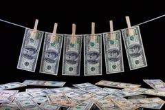 Billetes de banco sucios del dólar de EE. UU. que cuelgan de una cuerda para tender la ropa Imagen de archivo
