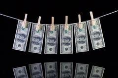 Billetes de banco sucios del dólar de EE. UU. que cuelgan de una cuerda para tender la ropa Fotos de archivo libres de regalías
