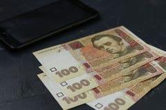 Billetes de banco ucranianos cientos hryvnia y smartphones, fondo del dinero imagen de archivo