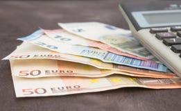 Billetes de banco y calculadora Billetes de banco euro en fondo de madera Foto para el impuesto, el beneficio y el cálculo del co Imagen de archivo