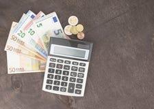 Billetes de banco y calculadora Billetes de banco euro en fondo de madera Foto para el impuesto, el beneficio y el cálculo del co Fotos de archivo libres de regalías