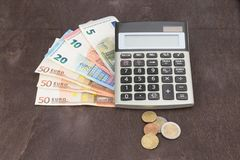Billetes de banco y calculadora Billetes de banco euro en fondo de madera Foto para el impuesto, el debe y el cálculo del coste Imagen de archivo